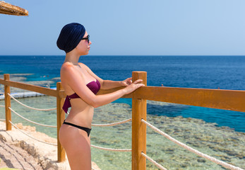 Young beautiful woman in female turban and sunglasses standing i