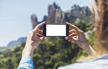 Hipster girl making photo on smartphone mobile closeup, view tourist hands using gadget phone in travel on background mountains and landscape; finger touch cellphone mockup nature, templates
