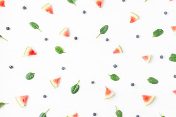 Watermelon slices, blueberry and spinach leaves on white background. Summer concept. Flat lay, top view