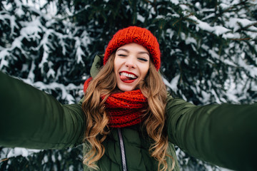 Winter selfie. Young happy girl in red knitted hat and scarf takes selfie and play the ape in winter cold day. Girl takes winter selfie