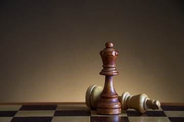 Dark queen defeats king in chess game, symbol of victory on the chessboard, wooden chess figures on a brown gradient background