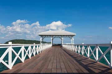 Wooden walk way leading to white pavilion on the seacoast skyline, Thailand
