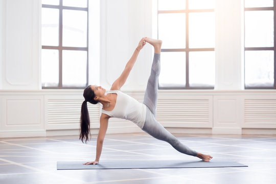 Young woman in white doing yoga pose
