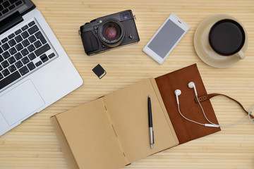 Vintage hipster wood top Desk, the laptop and a Cup of coffee, a camera, a leather notebook, a telephone