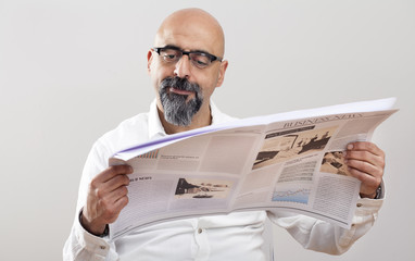 Middle aged man reading newspaper