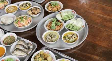 Set of Thai food on tray Fried Mackerel with Shrimp Paste Sauce, Fried Egg with Climbing Wattle, Chicken Green Curry, Spicy minced pork, Noodles rice with curry, Stir-fried noodles on wooden floor