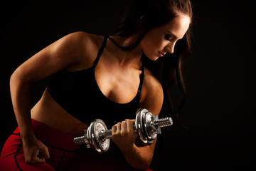 Beautiful young woman works out with dumbbells in fitness gym