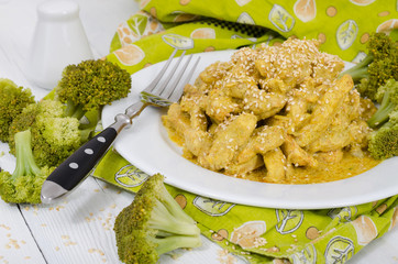 Close up view of chicken with curry sauce and sesame