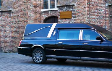 Leichenwagen vor Kirche mit Textfreiraum auf Schild