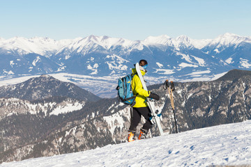 Female skier taking a look at landscape from the top of a mountain