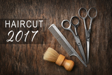 Vintage barber equipment and text HAIRCUT 2017 on wooden background