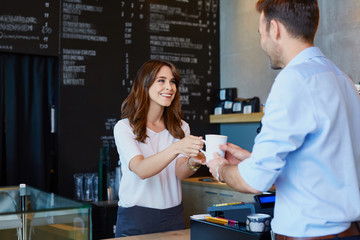 Young barista serving coffee to male customer in cafe