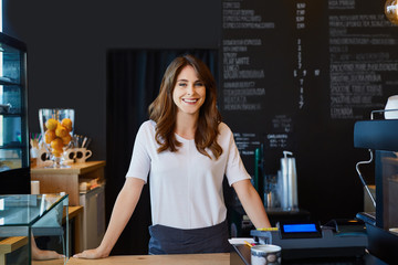 Beautiful female barista standing behind the bar in cafe