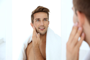 Young man standing in front of mirror and touching his face