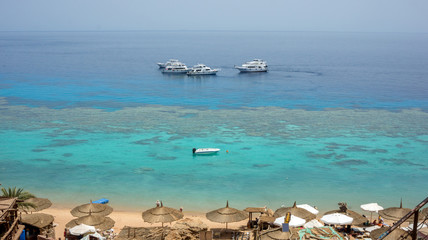 An amazing clear Red sea with coral reefs. Boats, umbrellas, sun beds. Farsha beach sharm el sheikh, Egypt
