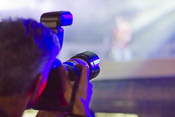 Fotógrafo realizando reportaje en un concierto de mùsica pop