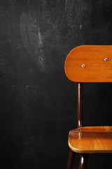Wooden school chair against blackboard