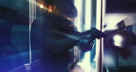 Einbrecher mit Pistole und Taschenlampe