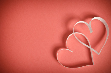 Two hearts of white paper lying on a red background