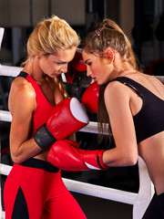 Two boxing women workout in fitness class. Sport exercise two female people .Boxer wearing red gloves to box in ring.