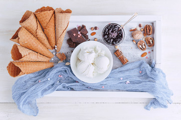 a tray of ice cream, jam and cups of powder on a wooden background