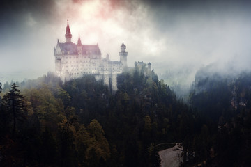 Aluminium Prints Castle Neuschwanstein castle in Germany, Bavaria. Artistic post-production stylized as ominous palace of dark forces, ominous clouds and mist at background and red glowing light over pinnacle castle tower.