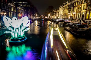 AMSTERDAM, NETHERLANDS - JANUARY 11, 2017: Cruise boats rush in night canals. Light installations on night canals of Amsterdam within Light Festival. January 11, 2017 in Amsterdam - Netherland..