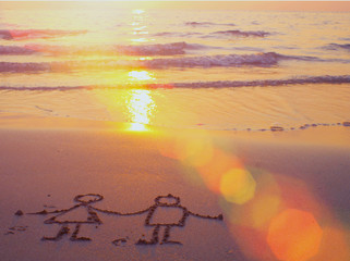 Sunset on the beach and romantic drawing in the sand.