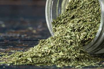 Dill weed spilling from a spice jar