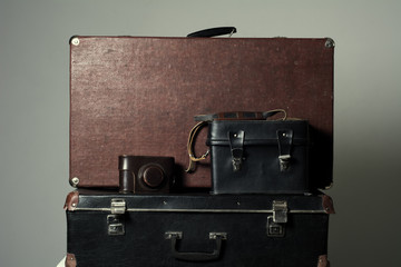 Background stack of old shabby suitcases and the camera