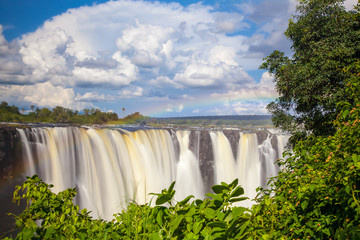 Victoria Falls.  Frontal view with a rainbow.  Taken with an MD filter.  Blue sky with clouds looming.