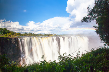 Wall Mural - Victoria Falls.  Frontal view with a rainbow.  Taken with an MD filter.  Blue sky with clouds looming.