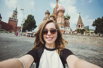 Pretty young woman tourist takes selfie portrait on the Red Square in Moscow, Russia. Beautiful female student takes photo for travel blog.