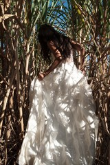 Beautiful Bride with white wedding dress in nature with sugar cane field background, romantic and picturesque photography