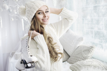 Portrait of young beautiful happy smiling girl holding skates and looking at camera. Model wearing stylish white knitted hat and clothes. Indoor. Day light. Christmas, New year, winter holidays