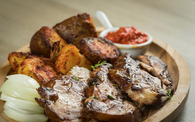 Grill special - chicken fillet cuts of smoked chicken drumstick meat, served with tasty baked potatoes and onions