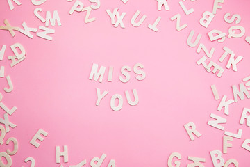 Sorting letters MISS YOU on pink.