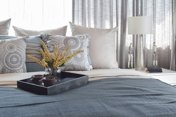 luxury bedroom interior with striped pillows and decorative tea set on bed