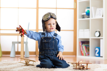 Child dressed like pilot aviator plays with a toy airplanes at home in his room