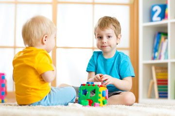 Children playing with logical educational toys, arranging and sorting shapes or sizes