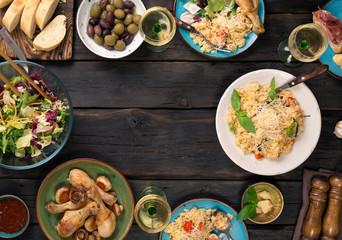 Frame of risotto, salad, appetizer, chicken drumsticks on wooden