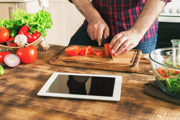 Man looking recipe on digital tablet and cooking healthy food