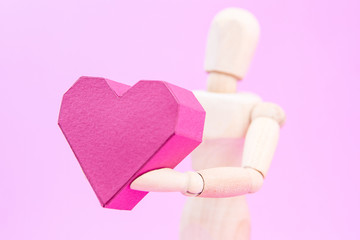 Wooden dummy holding paper box red heart shape on pink backgroun