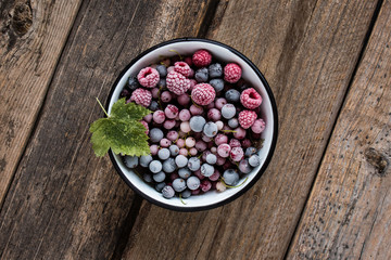 frozen berries, black currant, red currant, raspberry, blueberry in enamelled bowl decorated by currant leaf on wooden table in rustic style,  top view.