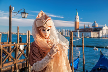 Famous carnival mask against gondolas in Venice, Italy