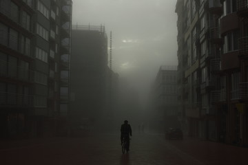 Cyclist on a street in foggy city
