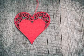 Valentine's card. Wooden red carved heart over wooden table background with copy space.