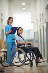 Female nurse assisting patient on wheelchair in corridor