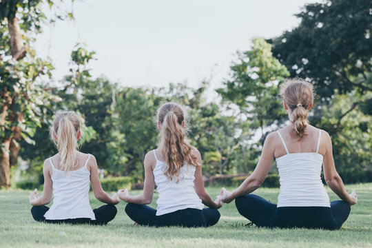 Mother and daughter doing yoga exercises on grass in the park at