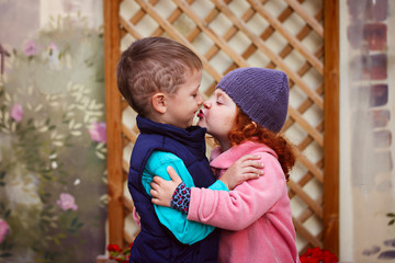 Little girl kissed for the first time adorable little boy. Love and romantic concept